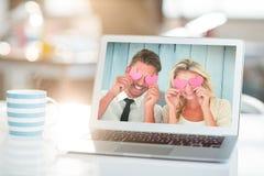 Image composée de jeunes couples tenant les coeurs roses au-dessus des yeux Image libre de droits