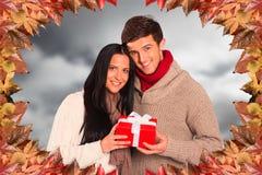 Image composée de jeunes couples tenant un cadeau Images libres de droits