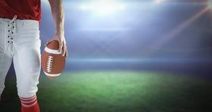 Image composée de joueur de football américain retardant le football Photographie stock