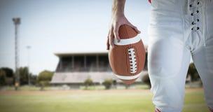 Image composée de joueur de football américain tenant le football Photographie stock libre de droits