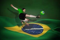 Image composée de joueur de football dans des coups de pied verts Image libre de droits
