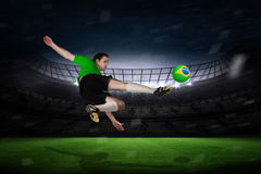 Image composée de joueur de football dans des coups de pied verts Photos libres de droits