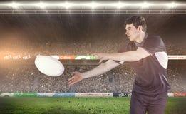 Image composée de joueur de rugby faisant un passage latéral Image stock