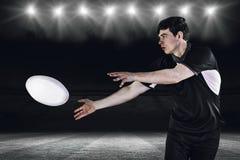 Image composée de joueur de rugby faisant un passage latéral Photographie stock libre de droits