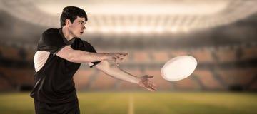 Image composée de joueur de rugby faisant un passage latéral Photographie stock