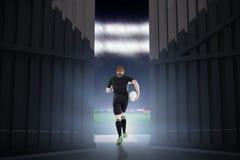 Image composée de joueur de rugby fonctionnant avec une boule de rugby 3d Photographie stock libre de droits