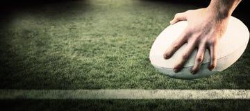 Image composée de joueur de rugby posant des pieds sur la boule Photos libres de droits