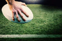 Image composée de joueur de rugby posant des pieds sur la boule Photo libre de droits