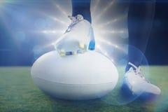 Image composée de joueur de rugby posant des pieds sur la boule Photo stock