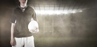 Image composée de joueur de rugby tenant une boule de rugby Photographie stock