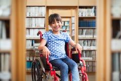 Image composée de l'élève handicapé mignon souriant à l'appareil-photo dans le hall photo libre de droits