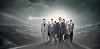 Image composée de l'équipe de sourire d'affaires regardant l'appareil-photo Photo libre de droits