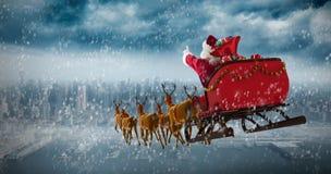 Image composée de l'équitation du père noël sur le traîneau avec le boîte-cadeau Photo libre de droits