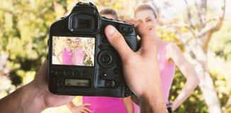 Image composée de l'image cultivée des mains tenant l'appareil-photo Photographie stock