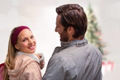 Image composée de l'homme de sourire ayant le bras autour de l'amie regardant l'appareil-photo Photo stock