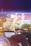 Image composée de l'homme de sourire employant des verres de réalité virtuelle tout en se reposant sur le fauteuil roulant Photo stock