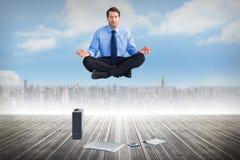 Image composée de l'homme se reposant dans la pose de lotus avec le comprimé et la valise d'ordinateur portable Photos libres de droits