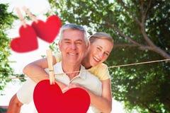 Image composée de l'homme supérieur heureux donnant à son associé un ferroutage Image stock