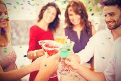 Image composée de l'image cultivée de la main grillant le cocktail Image libre de droits