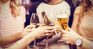Image composée de l'image cultivée des amis grillant avec de la bière et le vin Photographie stock