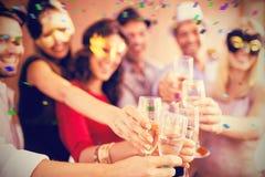 Image composée de l'image cultivée des mains tenant la cannelure de champagne Photo stock