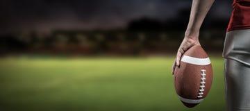 Image composée de l'image cultivée du joueur de football américain tenant la boule Image stock