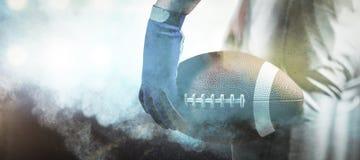 Image composée de l'image cultivée du sportif tenant la boule de boule de football américain Photos stock