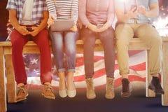 Image composée de la basse section des gens d'affaires s'asseyant sur le bureau photographie stock