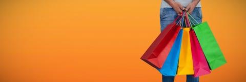 Image composée de la basse section de l'homme portant le panier coloré se tenant contre le backgrou blanc photographie stock