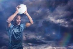 Image composée de la boule de rugby de lancement de sportif sûr 3D Photo stock