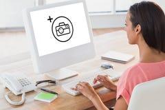 Image composée de la femme d'affaires à l'aide de l'ordinateur au bureau dans le bureau créatif Photo libre de droits