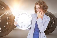 Image composée de la femme d'affaires inquiétée regardant l'horloge Photo stock
