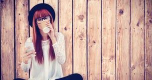 Image composée de la femme de sourire de hippie à l'aide de son smartphone Photographie stock