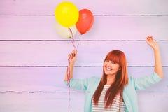 Image composée de la femme de sourire de hippie tenant des ballons Image stock