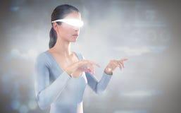 Image composée de la femme employant les verres visuels virtuels sur le fond blanc Images libres de droits