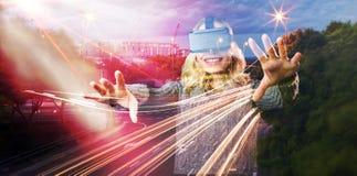 Image composée de la femme gaie à l'aide du casque virtuel de réalité photo stock