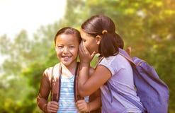 Image composée de la fille avec le sac à dos chuchotant dans l'oreille d'ami Images libres de droits
