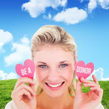 Image composée de la jeune blonde attirante tenant de petits coeurs Photos libres de droits