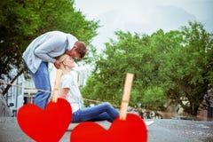 Image composée de la jeune séance blonde de hanche sur la planche à roulettes avec le front de baiser d'ami Image stock