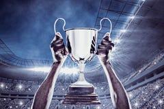 Image composée de la main cultivée de l'athlète tenant le trophée Photographie stock libre de droits