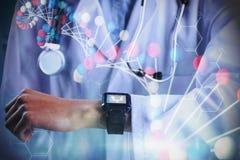 Image composée de la mi section du docteur féminin montrant la montre intelligente photo libre de droits