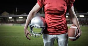 Image composée de la mi section du sportif tenant le football américain et le casque Image libre de droits