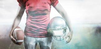 Image composée de la mi section du sportif tenant le football américain et le casque Images stock