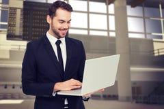 Image composée de la position de sourire d'homme d'affaires et de l'ordinateur portable d'utilisation Photos stock
