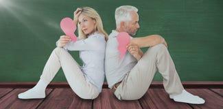 Image composée de la séance malheureuse de couples tout en tenant le coeur brisé Image libre de droits