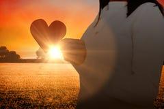 Image composée de la section médiane de la femme tenant le papier de forme de coeur Photographie stock libre de droits
