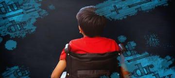 Image composée de la vue arrière du garçon se reposant dans le fauteuil roulant Photographie stock libre de droits