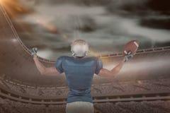 Image composée de la vue arrière du joueur de football américain tenant la boule photographie stock