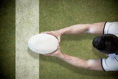 Image composée de la vue courbe de l'homme tenant la boule de rugby avec les deux mains Image stock
