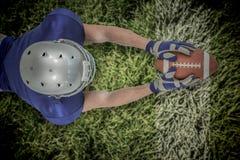 Image composée de la vue courbe du joueur de football américain atteignant vers la boule Images stock